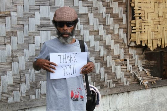 "Man holding a hand written sign saying ""Thank You"":"