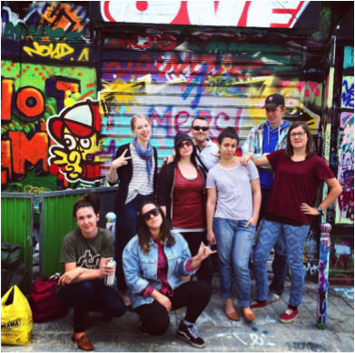 YWAM Paris Staff standing in front of graffiti on a wall