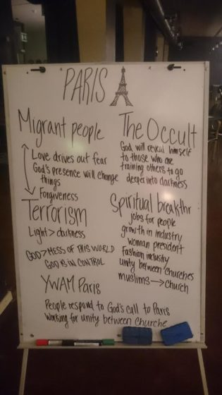 "Paris prayer white board - ""Migrant People, Terrorism, The Occult, YWAM Paris, Spiritual Breakthrough""."